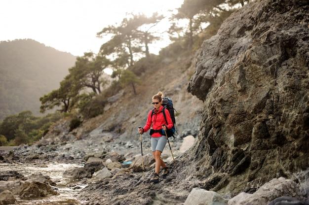 Mulher com caminhadas equipamentos trekking pela costa stoney