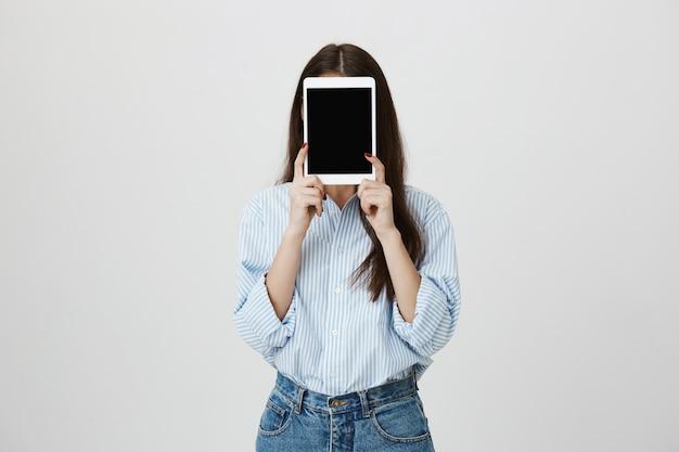 Mulher com camisa e rosto coberto com tablet digital, mostrando a tela
