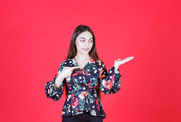 Mulher com camisa floral em pé na parede vermelha e apontando para a direita.