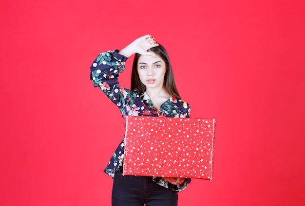Mulher com camisa floral segurando uma caixa de presente vermelha com pontos brancos e parece confusa e pensativa.