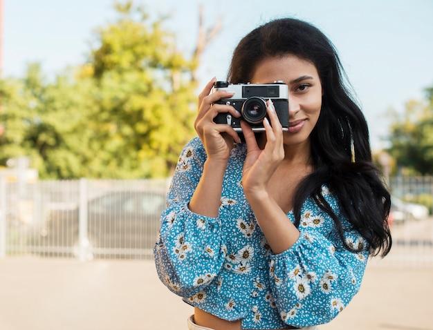 Mulher com camisa floral, tirando uma foto com uma câmera retro