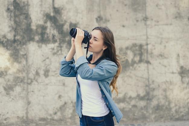 Mulher com camisa jeans tirando foto no fundo da parede cinza