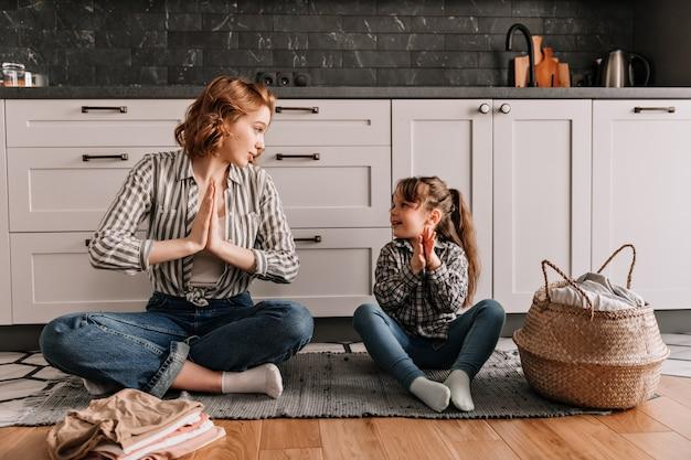 Mulher com camisa listrada está sentada no chão e mostra à filha como meditar.