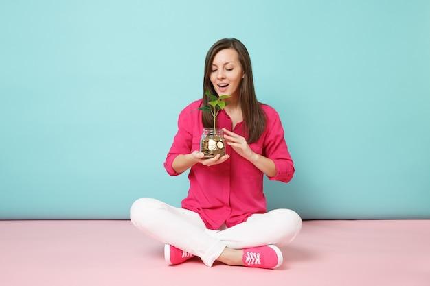 Mulher com camisa rosa e calça branca sentada no chão segurando moedas de ouro em uma jarra de vidro