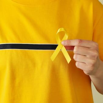 Mulher com camiseta amarela segurando fita de conscientização do câncer infantil