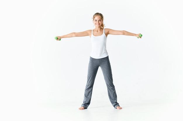 Mulher com camiseta branca com halteres nas mãos.