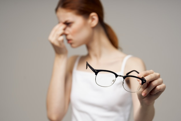 Mulher com camiseta branca de óculos problemas de visão miopia