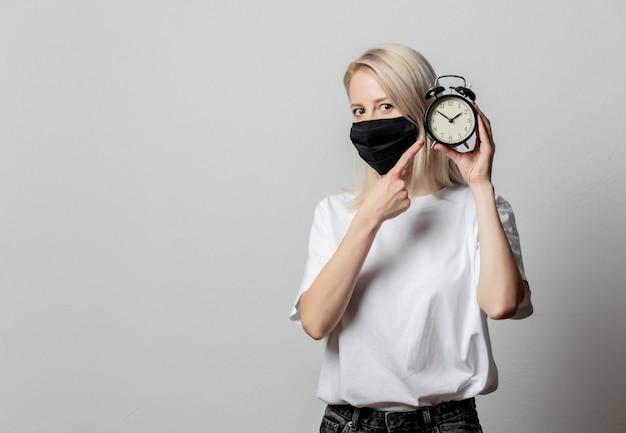 Mulher com camiseta branca e máscara preta com despertador na parede branca