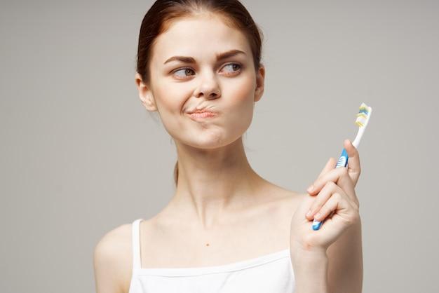 Mulher com camiseta branca, higiene dental, saúde, estúdio, estilo de vida