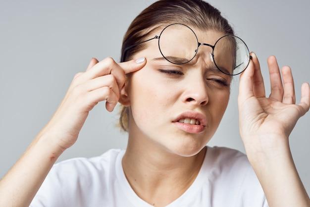 Mulher com camiseta branca, óculos, visão deficiente, close up