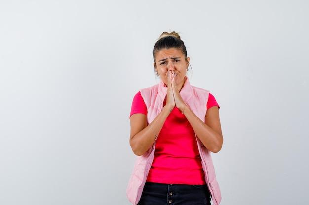Mulher com camiseta e colete de mãos dadas em gesto de oração e parecendo desamparada