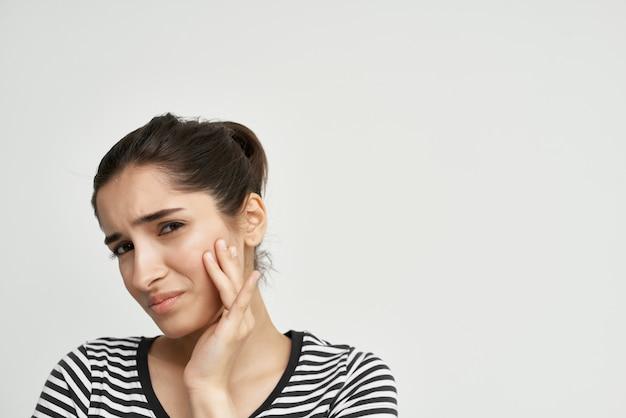 Mulher com camiseta listrada com dor no rosto durante tratamento dentário