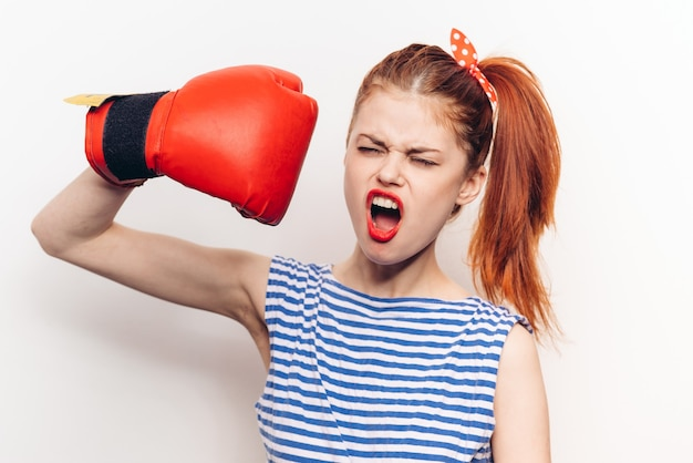 Mulher com camiseta listrada e luvas de boxe no treino