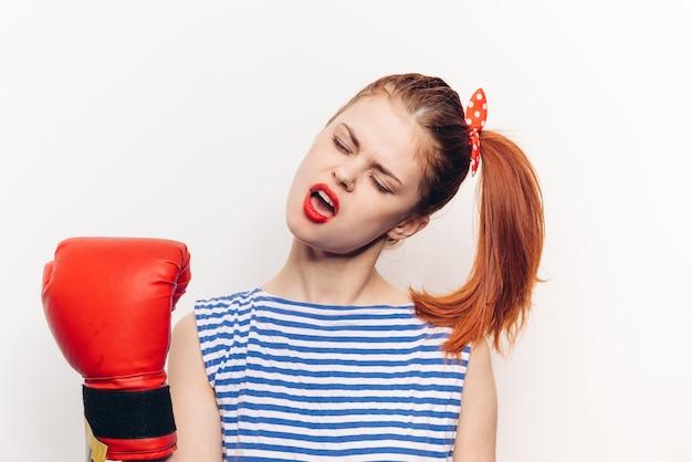 Mulher com camiseta listrada e luvas de boxe vermelhas esporte de agressão