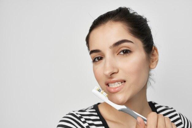 Mulher com camiseta listrada escovando os dentes, cuidados de higiene