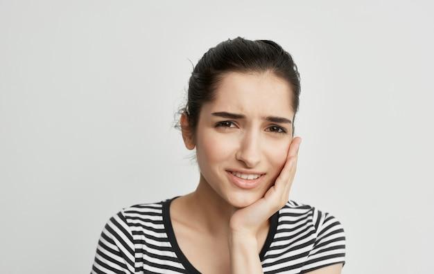 Mulher com camiseta listrada segurando rosto, problemas dentários, dor, descontentamento