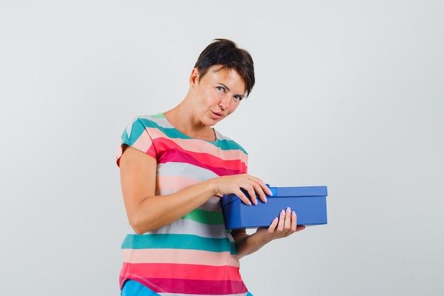 Mulher com camiseta listrada tentando abrir a caixa de presente e parecendo curiosa