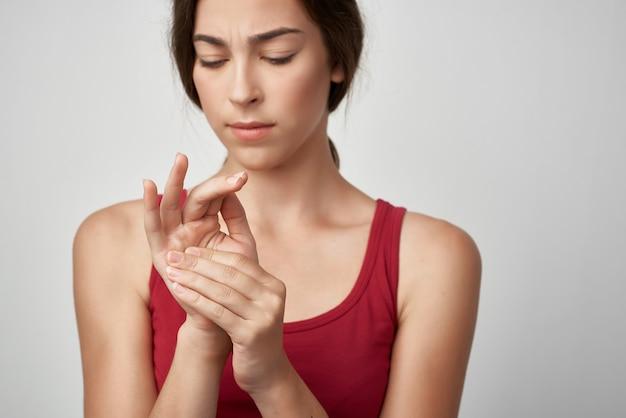 Mulher com camiseta vermelha dedo dor nas articulações
