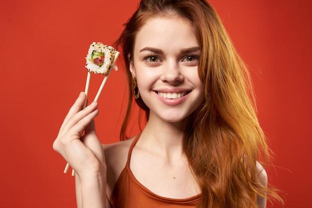 Mulher com camiseta vermelha pauzinhos sushi comida asiática