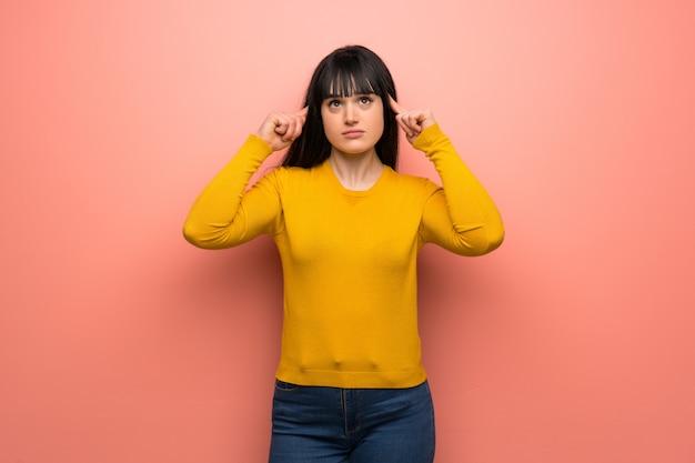 Mulher com camisola amarela sobre parede rosa com dúvidas e pensamento
