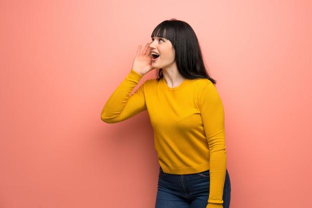 Mulher com camisola amarela sobre parede rosa gritando com a boca aberta para o lateral