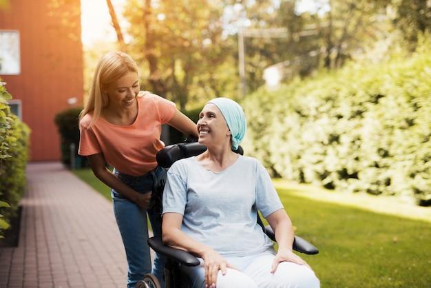 Mulher com câncer caminha na rua com a filha.