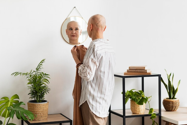 Mulher com câncer de pele se olhando no espelho