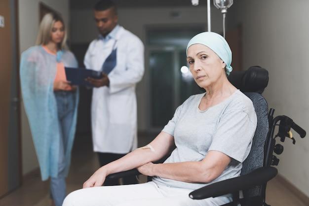 Mulher com câncer está sentado. filha fala com médico