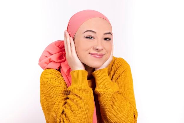 Mulher com câncer, vestindo um close de lenço rosa sobre fundo branco