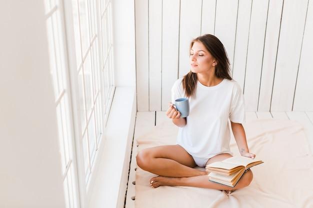 Mulher com caneca e livro, aproveitando a luz do sol