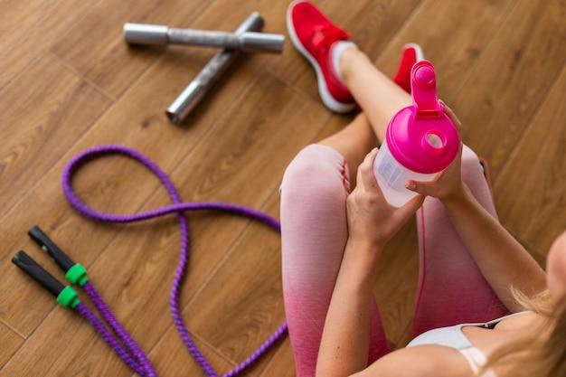Mulher com caneleiras cor de rosa e garrafa de água