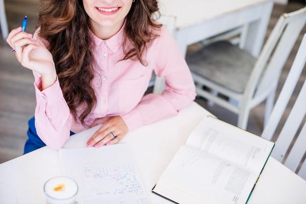Mulher, com, caneta, caderno, e, livro, tabela