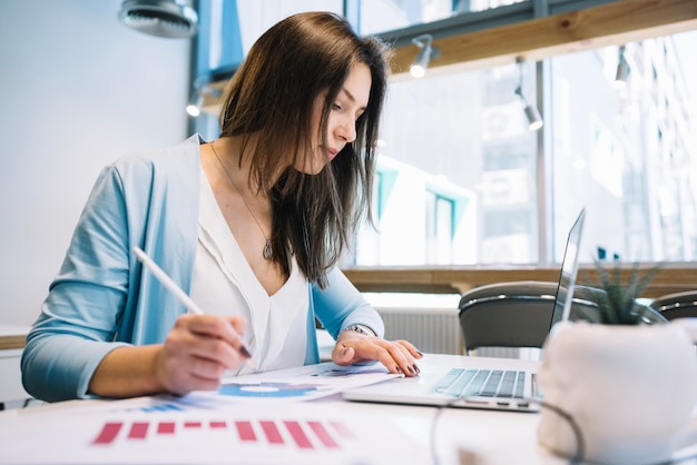 Mulher com caneta usando laptop