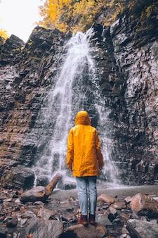Mulher com capa de chuva amarela no outono conceito de caminhada na cachoeira