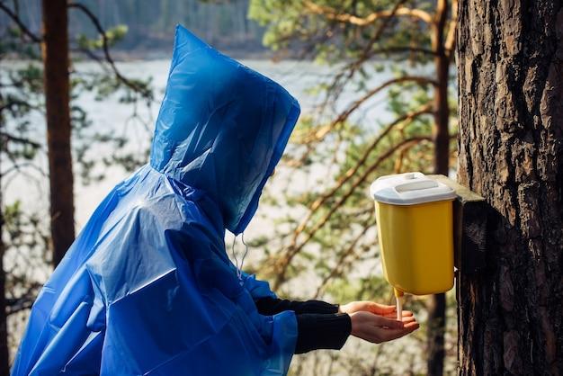 Mulher com capa de chuva azul lava as mãos na bacia pendurada na árvore. manhã depois da chuva no acampamento turístico na floresta perto do rio. o rosto da garota escondido pelo capuz. caminhadas estilo de vida.