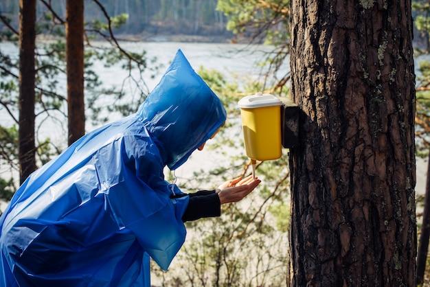 Mulher com capa de chuva azul lava as mãos na bacia pendurada na árvore.