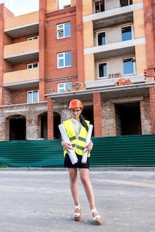 Mulher com capacete de construtor e colete segurando rolos de plantas