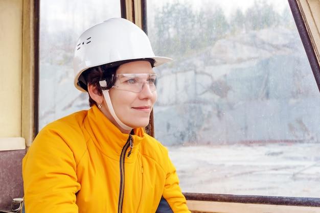 Mulher com capacete e óculos de proteção na cabine de equipamentos de construção pesada