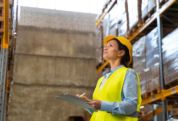 Mulher com capacete trabalhando em armazém