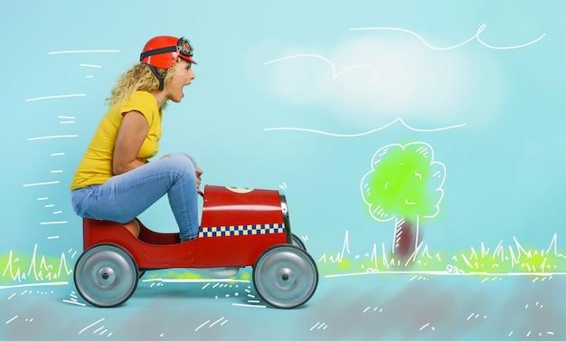 Mulher com capacete vermelho dirige um carro de brinquedo rápido. fundo ciano.
