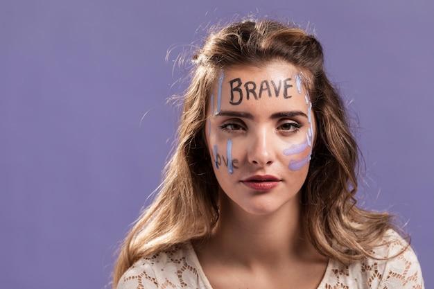 Mulher com capacitar palavras pintadas no rosto
