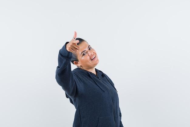 Mulher com capuz, apontando para a câmera e parecendo confiante, vista frontal.