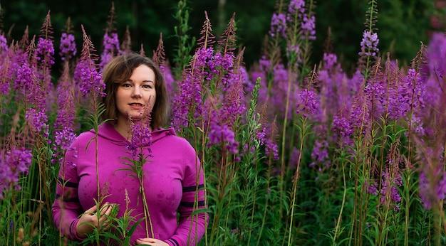 Mulher com capuz em meio a flores no prado