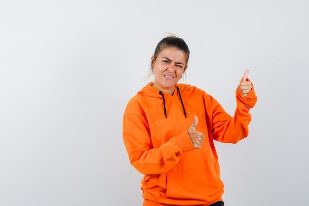 Mulher com capuz laranja mostrando dois polegares para cima e parecendo feliz