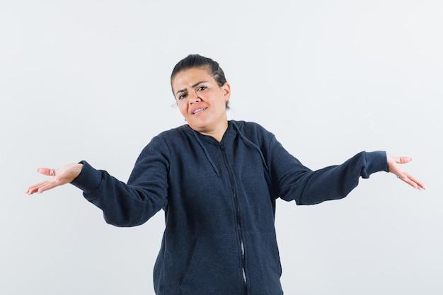 Mulher com capuz, mostrando um gesto desamparado e parecendo confusa, vista frontal.