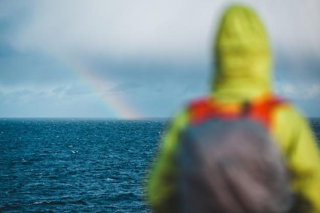 Mulher com capuz verde no mar