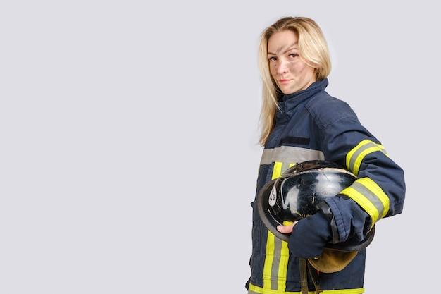 Mulher com cara suja em uniforme de bombeiro segurando capacete de segurança
