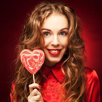 Mulher com caramelo de coração sobre fundo vermelho