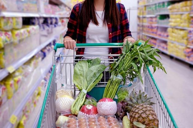 Mulher com carrinho de compras, comprar comida em um supermercado.
