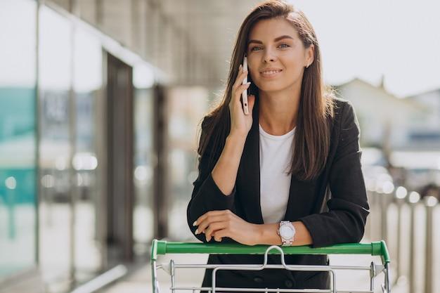 Mulher com carrinho de compras de supermercado falando ao telefone